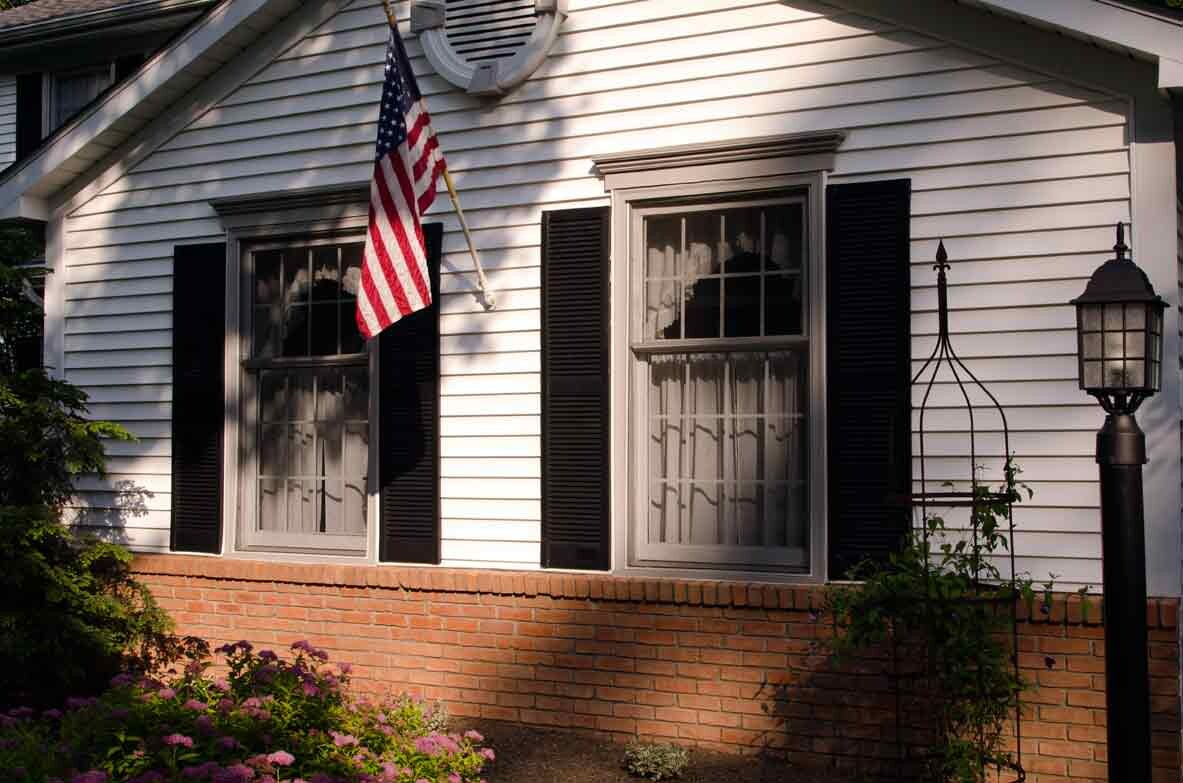 House with two window and have US flag at middle